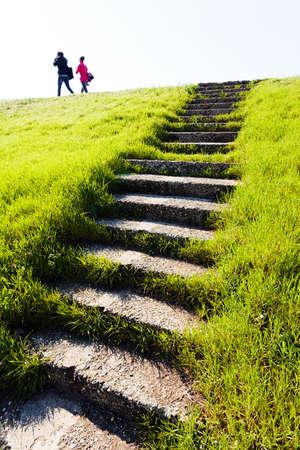 bajando escaleras: Escaleras de piedra viejas en campo de hierba con personas en la parte superior; vista desde abajo