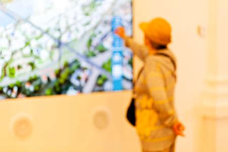 Uma mulher mais idosa tenta o showpiece na expo da tecnologia; desfocada 100% Foto de archivo - 93531170