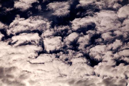 Pequeñas nubes blancas mullidas en el cielo oscuro, antes de la lluvia Foto de archivo - 93531022