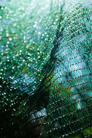 建設現場のための厚い緑色のプラスチックセーフティネット、フィールドの浅い深さに注意してください