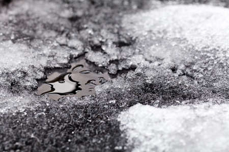 Tiny puddle of melting snow on asphalt