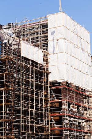 足場とクレーンで建設中の建物 写真素材