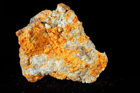 黒い背景にある硫化鉱物の realgar