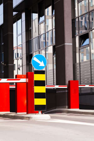 one lane road sign: Parking barrier and mandatory way sign, building in background