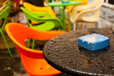Wet coffee shop table with blue ashtray on it