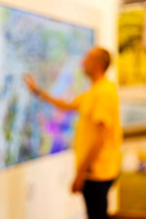 showpiece: Man in yellow t-shirt looking showpiece at technology expo; blurred 100%