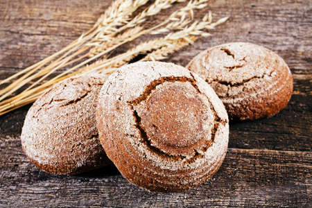 Decoration with a round rye bread and  dried branches of rye on a wooden board Stock Photo