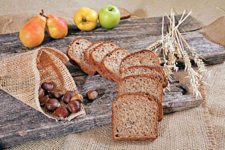 Decoration with rye bread on a wooden board with chestnuts in a cone, fruit and  dry twigs of grain around