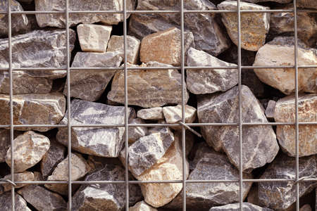 gabion mesh: large stones behind wire fences, note shallow depth of field