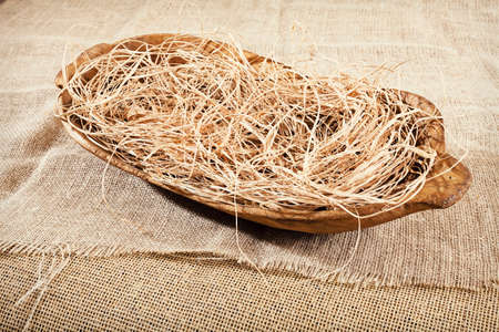 old wooden oval bowl with straw on a linen cloth Stock Photo - 87278640