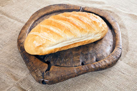 loaf of bread on an old wooden board Stock Photo - 87278689