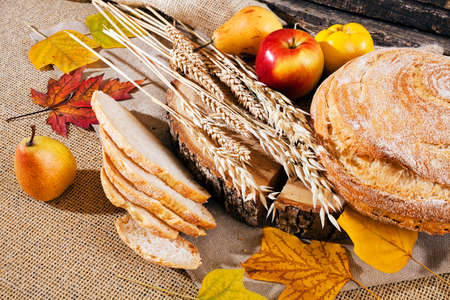 Decoration with bread, cereal and fruit on a linen background