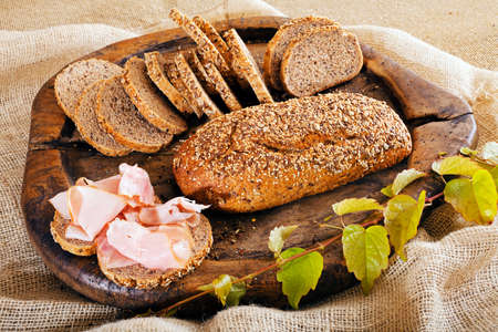 integral bread on the wood board with ham and green branch, note shallow depth of field