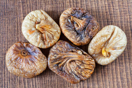 dried figs on a wooden table, note shallow depth of field