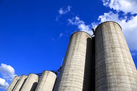 Concrete silos against a deep blue sky with room for text Stock Photo