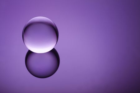Crystal ball floating on a purple background Stock Photo