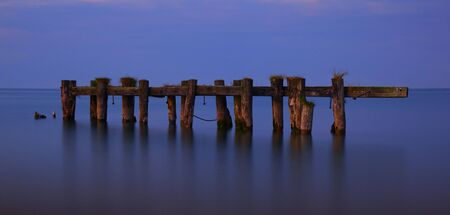 Warm evening light contrasts against a tranquil Lake Ontario as it highlights the remains of an aging pier completely separated from the shore.