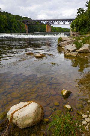 Train Bridge and Dam as seen from the Grand River shore near Paris, Ontario, Canada