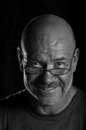 Dramatically lit head shot of older man looking over his glasses and smiling