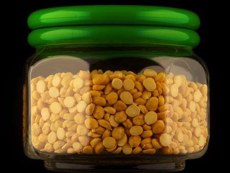 Glass container of chana dal isolated on black Stock Photo