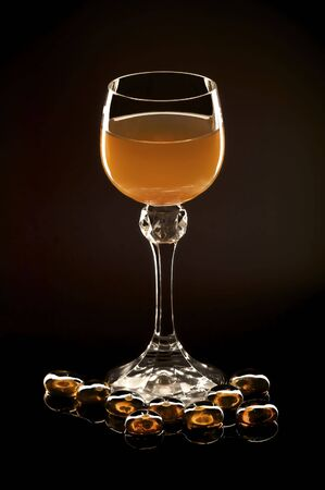 Photoillustration of a glass of amber nectar isolated on black