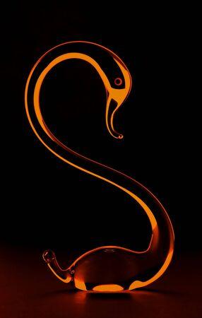 Glass swan backlit with golden light