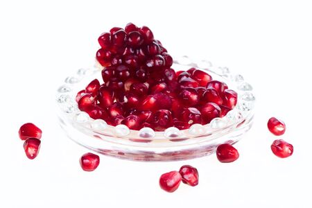 Serving of pomegranate in glass tray isolated on white