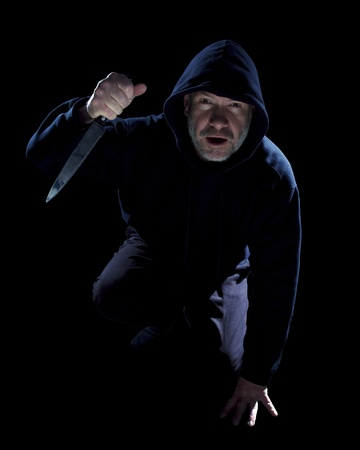 Crouching burglar with kitchen knife on black