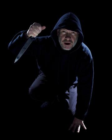 Crouching burglar with kitchen knife on black