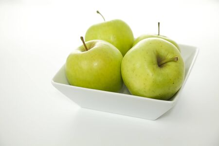 pectin: Green Crispin Mutsu Apples in a White Bowl on a White Background in Minimalist Style