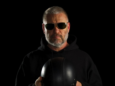 Biker on black background holding his half hat helmet
