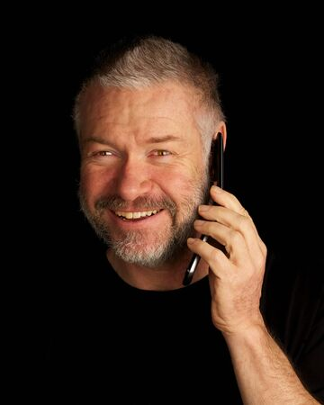 Man talking on cellphone and smiling on black background
