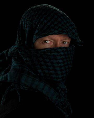 man wearing islamic headgear against a black background