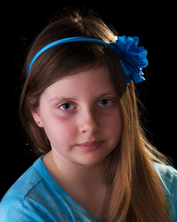 Young girl in blue with flower in her hair on black