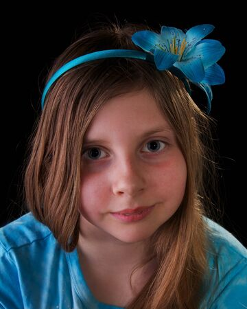 Young girl in blue with flower in her hair