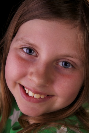 Closeup of blue eyed girl smiling on black background