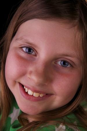 Closeup of blue eyed girl smiling on black background