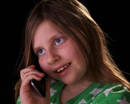 Young girl talking on her cell phone on black background