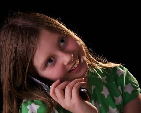 Young girl talking on cell phone and flipping her hair