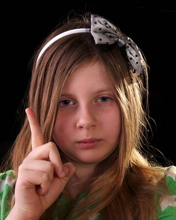 Young girl scolding and shaking her finger on black