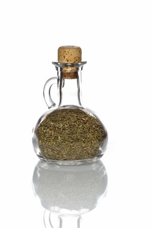 Thyme in a glass bottle with a cork and isolated with reflection on white