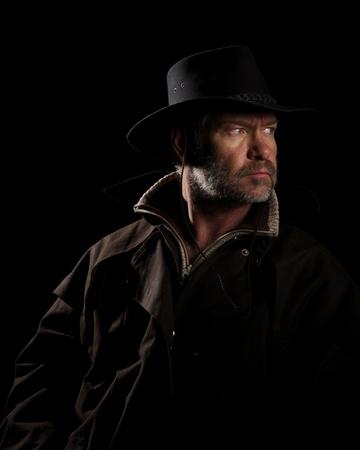 Rugged Cowboy on horseback looking intensley