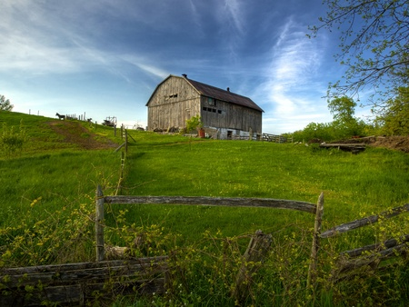 Rural Ontario farm scene of an old barn on a hill in spring time