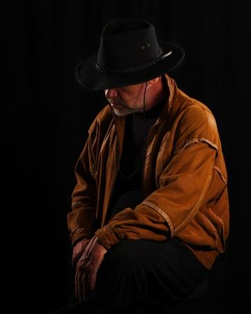 Cowboy sitting looking very sad on black background Stock Photo