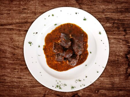 stewed goat in white plate on wooden table