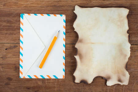 Old Burnt Paper and envelope on Wood background photo