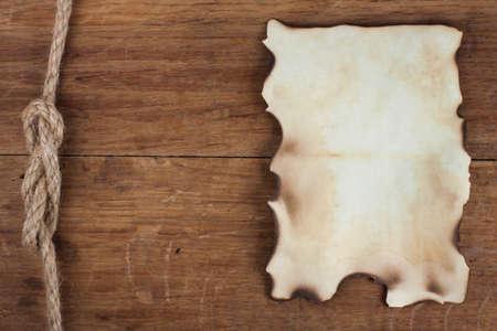Vecchia carta bruciata su sfondo legno Archivio Fotografico