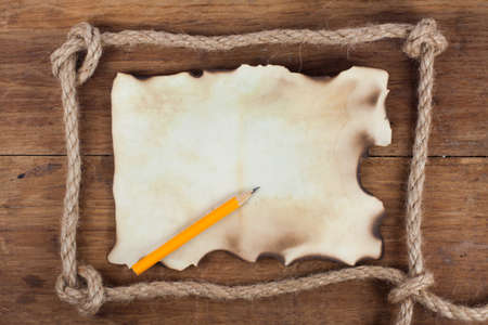 Old Burnt Paper and a Pencil in the Rope frame on a Wood background photo