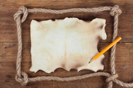 burnt wood: Old Burnt Paper and a Pencil in the Rope frame on a Wood background
