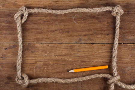 old pencil: Frame composed of Rope with pencil on a Wooden background
